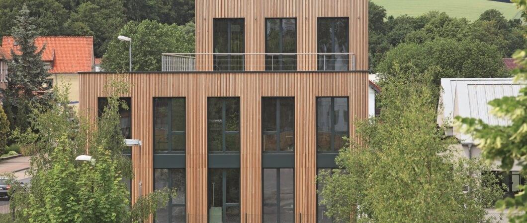 Фасад здания центра обслуживания клиентов облицован вертикальными деревянными планками.