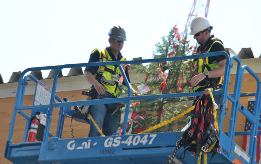 """Gray's Site Manager Kendall Kluttz, left, and EGGER's Construction Project Manager Christian Kasper, prepare to place a tree on the topmost beam of EGGER's new particleboard plant, part of an Austrian building tradition called """"topping off."""""""