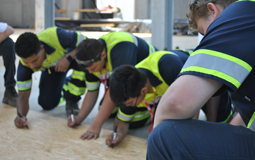 Students in EGGER's apprenticeship program sign an EGGER oriented strand board (OSB) during the topping off celebration to mark a milestone in construction of the company's first North American manufacturing facility.