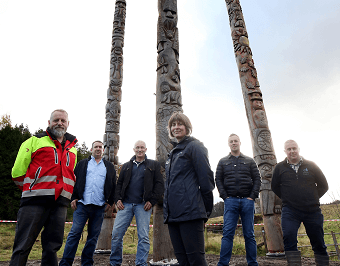 Pictured left to right with the new Stonehaugh totem poles are John Patterson, Robert Scott, Steve Batey, Ruth Dickinson, Shaun Rogerson and Alex MacLennan.