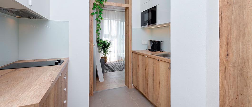 Dekor W1000 PG Premiově bílá v kombinaci s  H1180 ST37 Dub Halifax přírodní vytváří v kuchyni harmonický pocit.