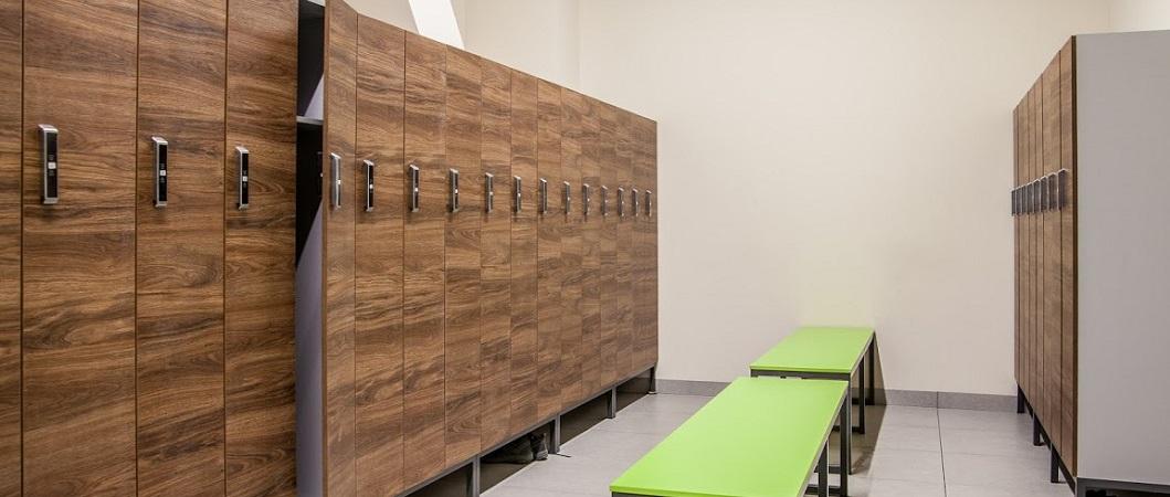 Шкафчики в раздевалках в декоре H3154 Дуб Чарльстон темно-коричневый сочетаются со скамейками в декоре U630 Зеленый лайм.