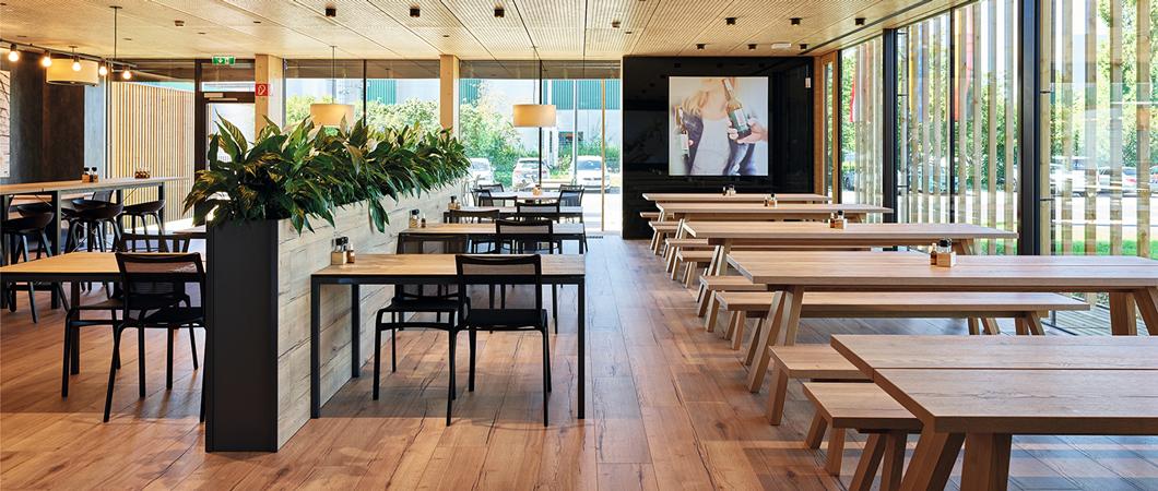 Ferestrele înalte până la plafon creează vizual o tranziție aproape invizibilă între interior și exterior.